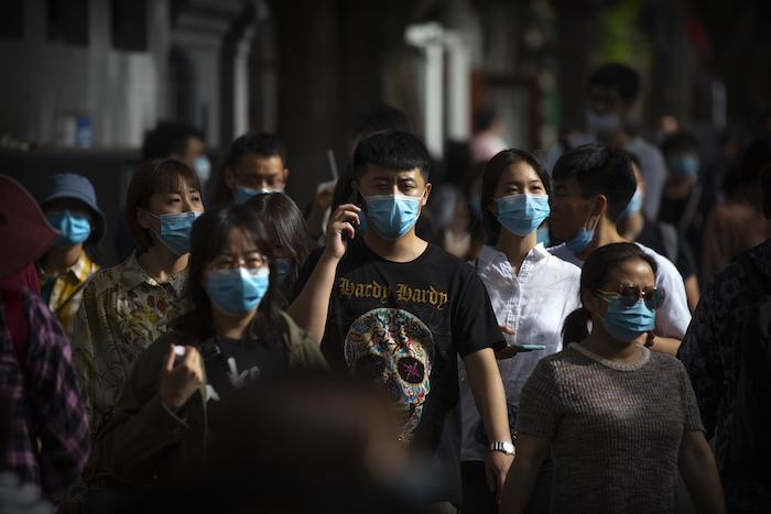 Personas con mascarillas para reducir los contagios de coronavirus caminan en una calle comercial en Beijing, el sábado 16 de mayo de 2020.