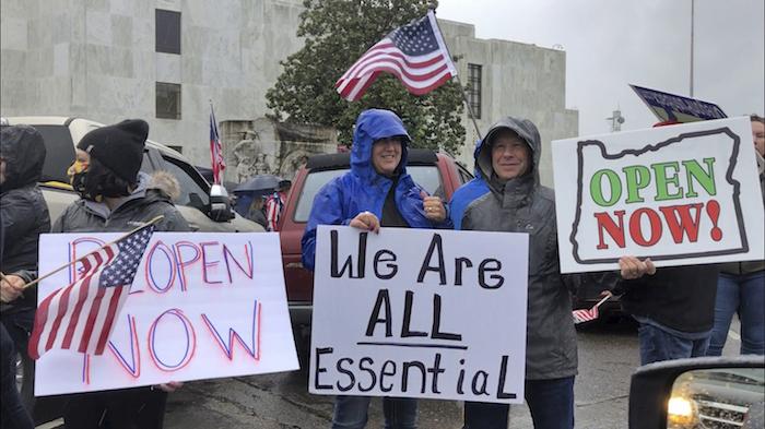 En esta imagen de archivo, tomada el 2 de mayo de un grupo de personas protestan con carteles contra la decisión ejecutiva de la gobernadora de Oregon, Kate Brown, de paralizar gran parte de la economía del estado e imponer la distancia social en un esfuerzo por frenar la pandemia del coronvirus, en una protesta en el exterior del capitolio estatal, en Salem, Oregon.