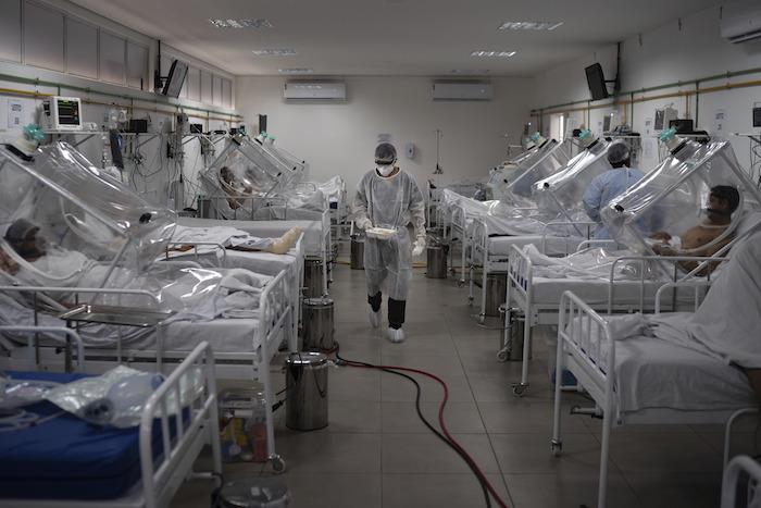 Pacientes de COVID-19 con un sistema de respiración asistida no invasiva llamado  'Cápsula Vanessa' en el hospital municipal de campaña Gilberto Novaes en Manaos, Brasil, el lunes 18 de mayo de 2020.