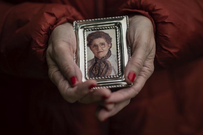 En esta imagen, tomada el 14 de mayo de 2020, Teresa Navarro muestra una fotografía de su madre, Concepción Rosinos, de 97 años, en Madrid, España.