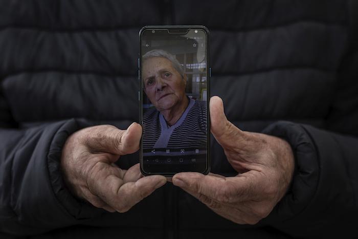 En esta imagen, tomada el 13 de mayo de 2020, Andrés Campos muestra una fotografía de su suegra, Carmen López, de 84 años, en Madrid, España.