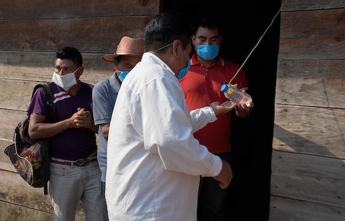 Fotografía del 12 de mayo de 2020, que muestra a indígenas que aplican medidas sanitarias en la comunidad de Chilón, en el estado de Chiapas (México).
