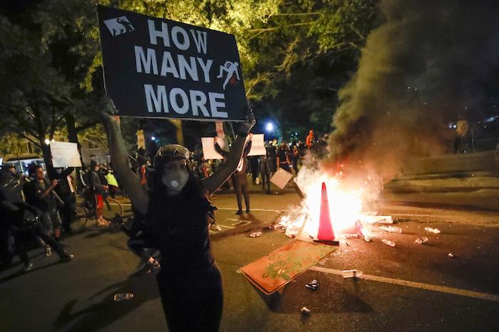 """Manifestantes protestan en Washington el domingo 31 de mayo de 2020, cerca de la Casa Blanca, por la muerte de George Floyd, quien falleció a manos de la policía en Minnesota. El letrero dice: """"¿Cuántos más?""""."""