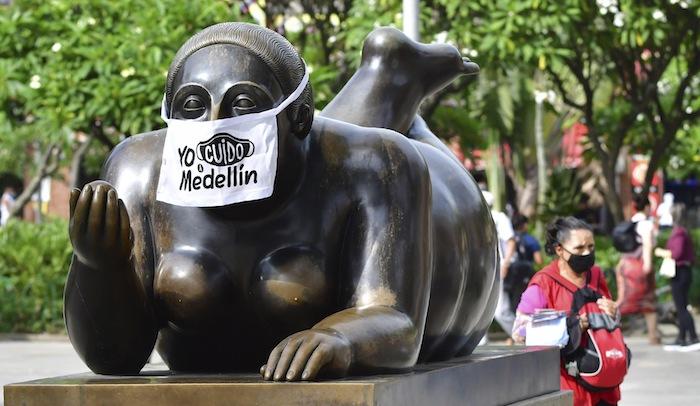 """Estatua callejera de Fernando Botero con un tapabocas que dice """"Yo cuido a Medellín"""" en foto del 9 de junio del 2020. Medellín tomó medidas temprano y ha logrado contener el brote de coronavirus. Tiene poco más de 800 contagios y apenas cuatro muertos."""