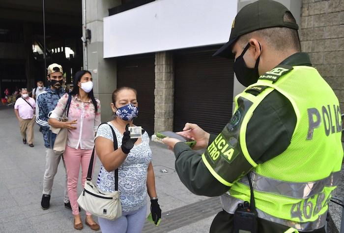 Un policía de Medellín usa un nuevo software para escanear documentos de identidad y determinar si una persona está autorizada a salir de su casa ese día en plena pandemia del coronavirus. Foto del 8 de junio del 2020.