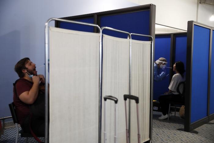 Personal médico realiza la prueba de detección del nuevo coronavirus a pasajeros de un vuelo procedente de Doha, Qatar, en el aeropuerto internacional Eleftherios Venizelos, en Atenas, el 15 de junio de 2020.
