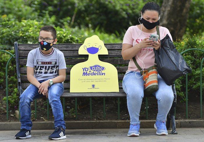Un cartel en un banco de Medellín recuerda a la gente que debe mantener distancias por el coronavirus en foto del 8 de junio del 2020.