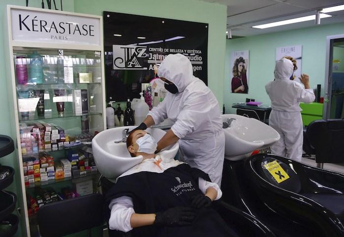 Una peluquera con un uniforme protector le lava el cabello a una clienta el 8 de junio del 2020 en Medellín, en plena pandemia del coronavirus.