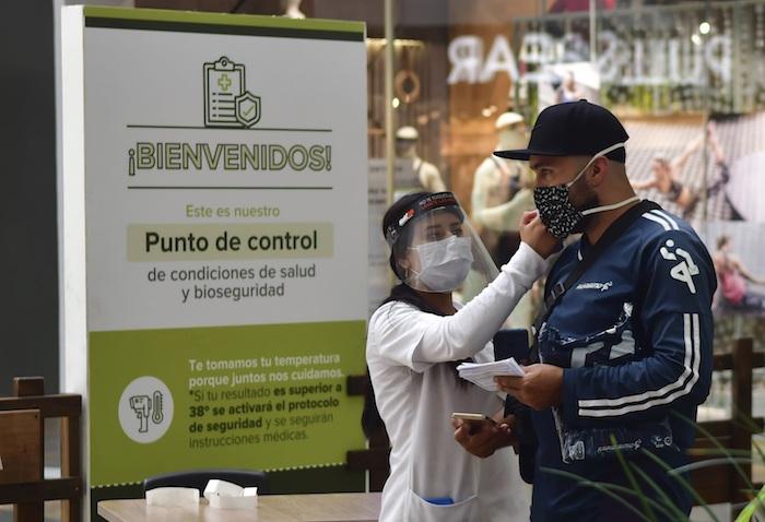 Una enfermera la mide la temperatura a un individuo en el centro comercial El Tesoro en Medellín el 9 de junio del 2020, en medio de la pandemia del coronavirus.