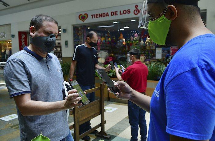 Empleado del centro comercial El Tesoro de Medellín usan teléfonos para escanear una aplicación de los teléfonos de los visitantes para asegurarse de que están autorizados a salir de sus casas durante la pandemia del corinavirus, en foto del 8 de junio del 2020.