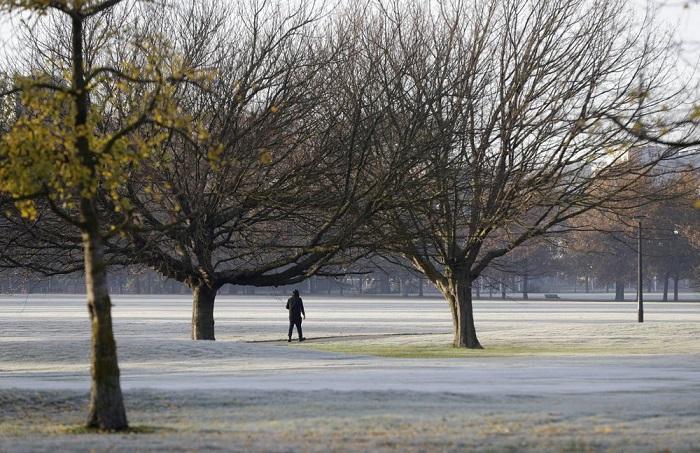 Un hombre camina por las calles cubiertas de escarcha de un campo de golf en el centro de Christchurch, Nueva Zelanda.