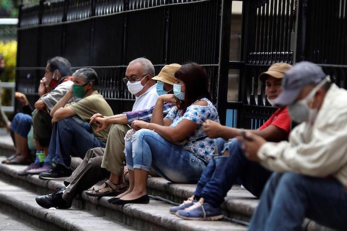 Un grupo de personas descansan en el Parque Central de Tegucigalpa (Honduras).