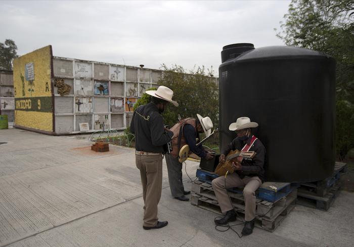 Un trío de músicos con mascarillas para protegerse del coronavirus espera clientes el jueves 9 de julio de 2020 en el cementerio municipal de Nezahualcóyotl, cerca de la Ciudad de México.