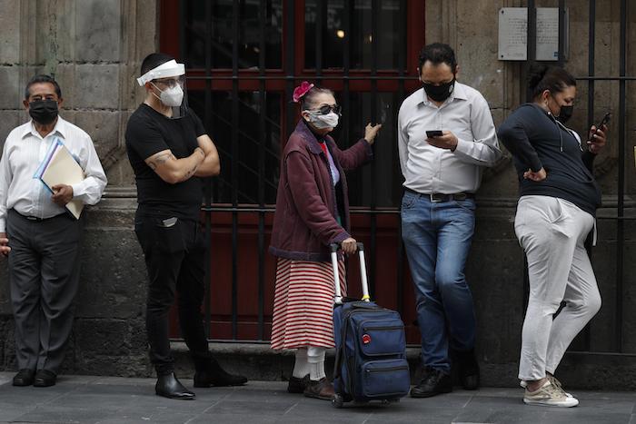 Varias personas con mascarillas para protegerse del coronavirus hacen fila antes de ingresar a un banco el lunes 6 de julio de 2020, en el centro de la Ciudad de México.