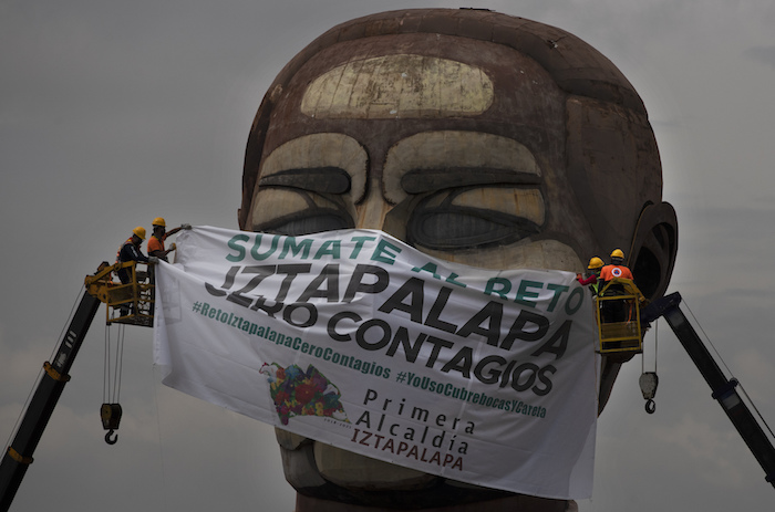 """Trabajadores de la ciudad colocan una mascarilla gigante con un texto escrito en español que dice """"Súmate al reto, Iztapalapa cero contagios"""", en el museo Cabeza de Juárez en medio de la pandemia de COVID-19, en Iztapalapa, Ciudad de México, el miércoles 12 de agosto de 2020."""