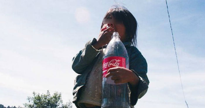Una niña con un envase de Coca-Cola.