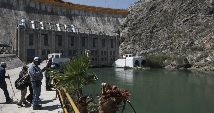Varios agricultores observan la presa La Boquilla, en el estado de Chihuahua, el miércoles 9 de septiembre de 2020 tras haberle quitado la víspera el control de la misma a la Guardia Nacional con el fin de cerrar las válvulas e interrumpir el flujo del agua que va a Estados Unidos.