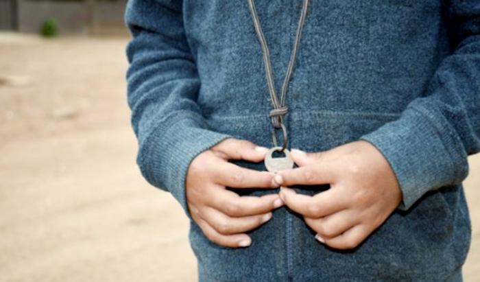 Un niño de cuatro años lleva la llave de su casa colgada en el pecho.