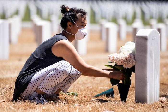 Una mujer deja flores en la tumba de una víctima mortal de la COVID-19.